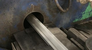 This photo shows an extrusion exiting the front of the press